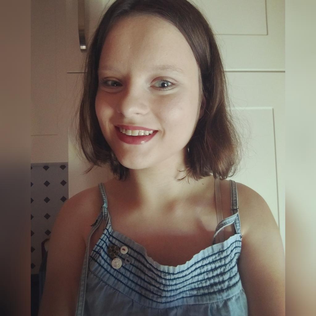 Selfie von justdisabled, innenraum, sie lächelt in die Kamera und trägt ein blaues Oberteil