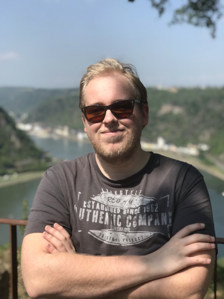 Ein Portait von Nwing. Er steht draußen, mit Sonnenbrille und Tshirt. Lächelt in die Kamera. Hinter ihm sieht man ein Ufer mit Wasser.