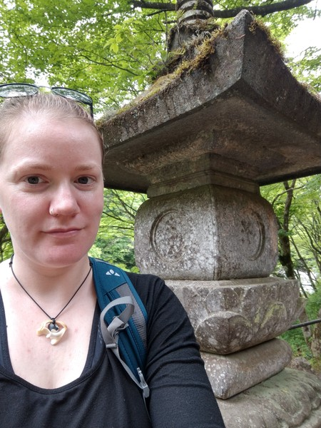 Selfie, draußen, Autistvsclichee steht vor einer Steinstatue und lächelt.