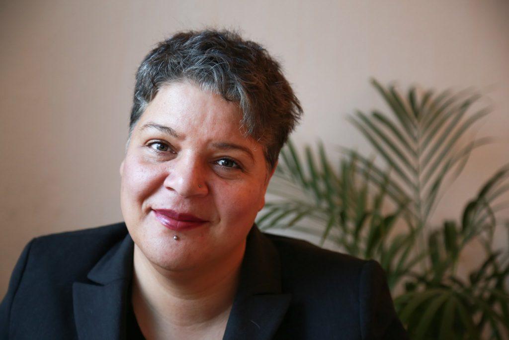 Drinnen Portraiftoto: Puja trägt: Ein schwarzes Sakko, roten Lippenstift, graue kurze Haare  und lächelt dabei in die Kamera