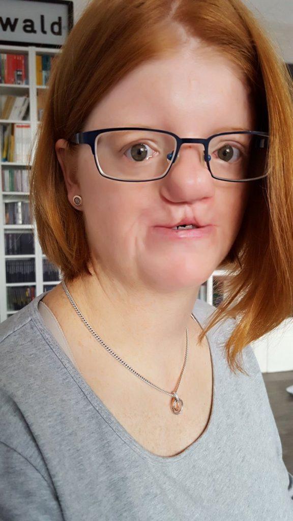Portrait drinnen: Anke trägt ihre Haare in einem roten Bob geschnitten. Schwarze Brille, graues Oberteil. An ihrer Oberlippe sieht man eine Spalte.