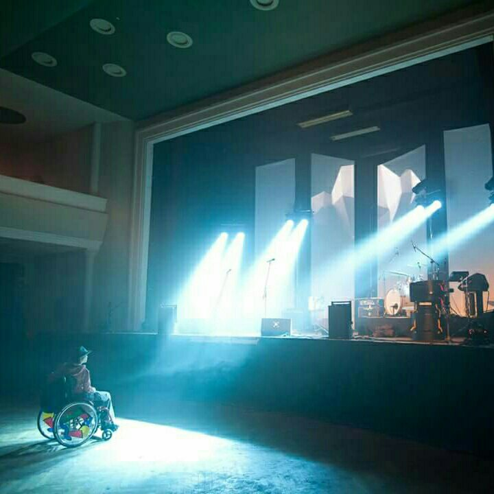 November_Crash steht im Rollstuhl in einer großen Halle und schaut auf eine Bühne. Von der Bühne leuchten Scheinwerfer auf sie. Auf der Bühne stehen verschiedene Musikinstrumente.