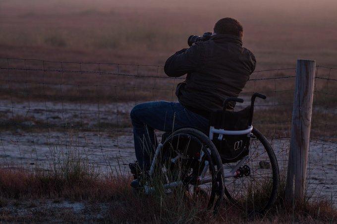 Das Bild zeigt Batsleia von hinten in der Natur. Er sitzt im Rollstuhl vor einem Zaun und fotografiert mit einer Kamera die Landschaft.