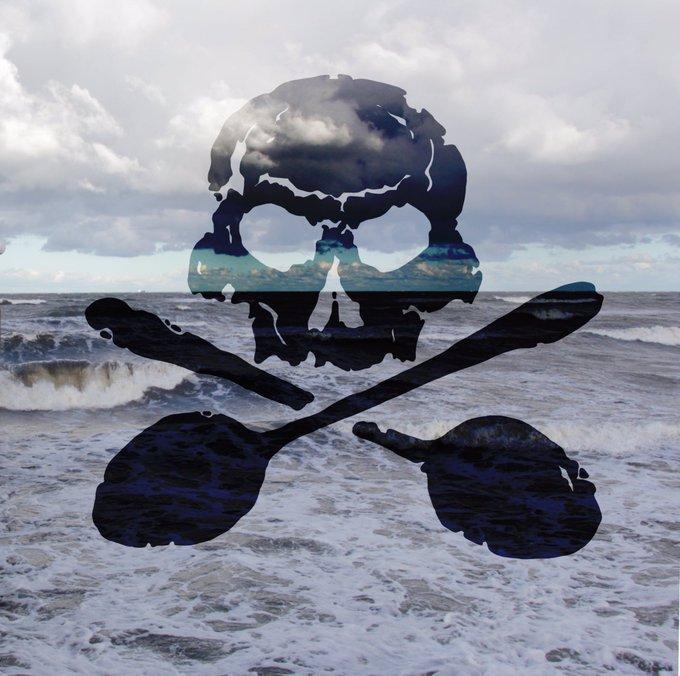 Ein schwarzer Totenkopf mit gekreuzten Löffeln vor einen Meerbild