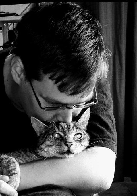 LiLaLuka hält eine Katze im Arm und beugt sich zu ihr herunter. Das Foto ist in Schwarz-Weiß.