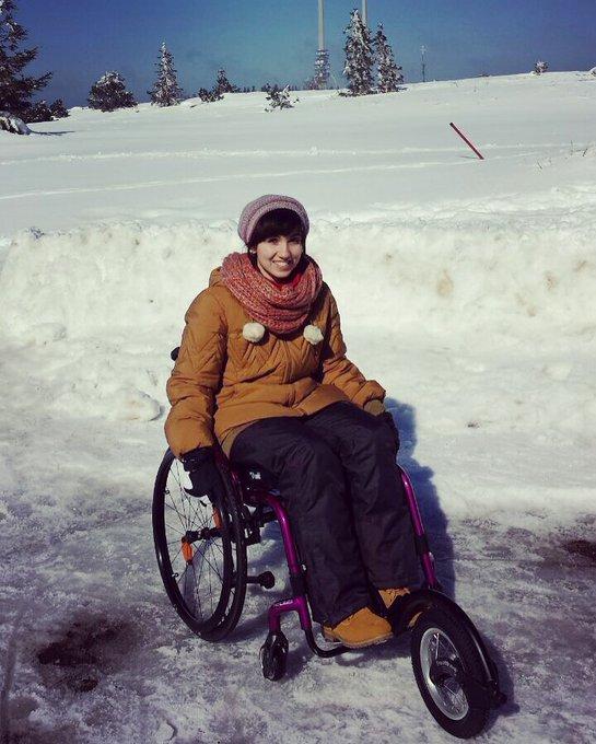 Lisa sitzt im Rollstuhl. Um sie herum ist Schnee. Sie trägt Mütze, Jacke, Hose,Schuhe, Schal und Handschuhe in schwarz und Orangentönen. Vorne am Rollstuhl ist ein 5. extra Rad montiert.