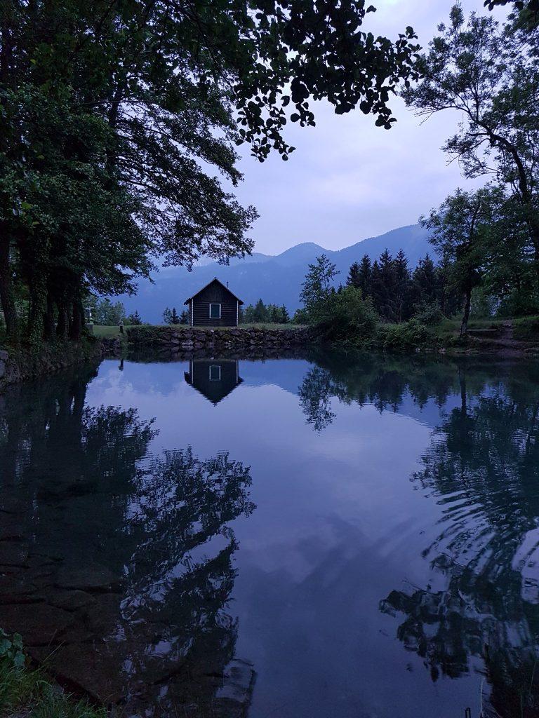 Ein See mit Bäumen drum herum.  In der Ferne sieht man ein kleines Haus und im Hintergrund sind Berge zu erkennen.