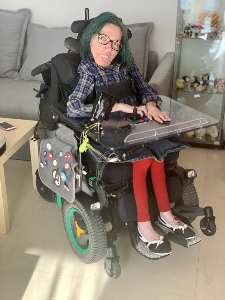 Melly trägt grüne mittellange Haare, eine rote Leggins und eine dunkle Brille. Sie nutzt einen grün-schwarzen E-Rollstuhl. Ihre Hände liegen auf dem Glastisch am Rollstuhl.