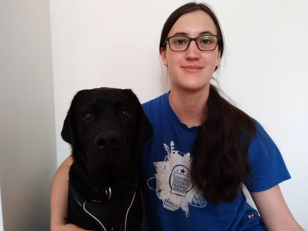 drinnen, Bluetenstille lächelt in die Kamera, sie trägt: schwarze, lange Haare, Brille und ein blaues Shirt. Neben ihr sitzt ein großer schwarzer Hund.