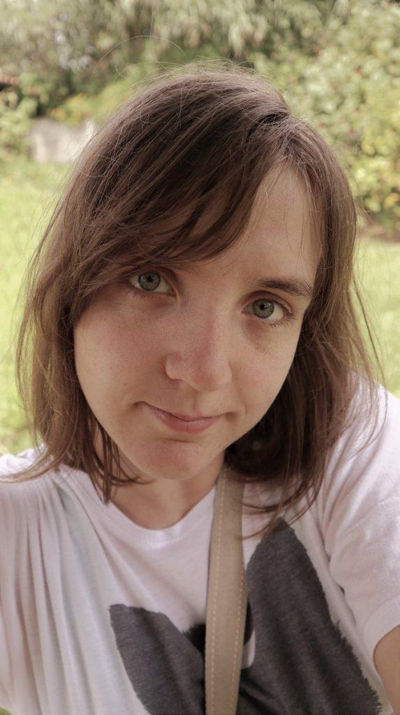 Potraitbild draussen. Sunaya, trögt mittelange braune haare, ein weißes shirt und schaut direkt in die kamera.