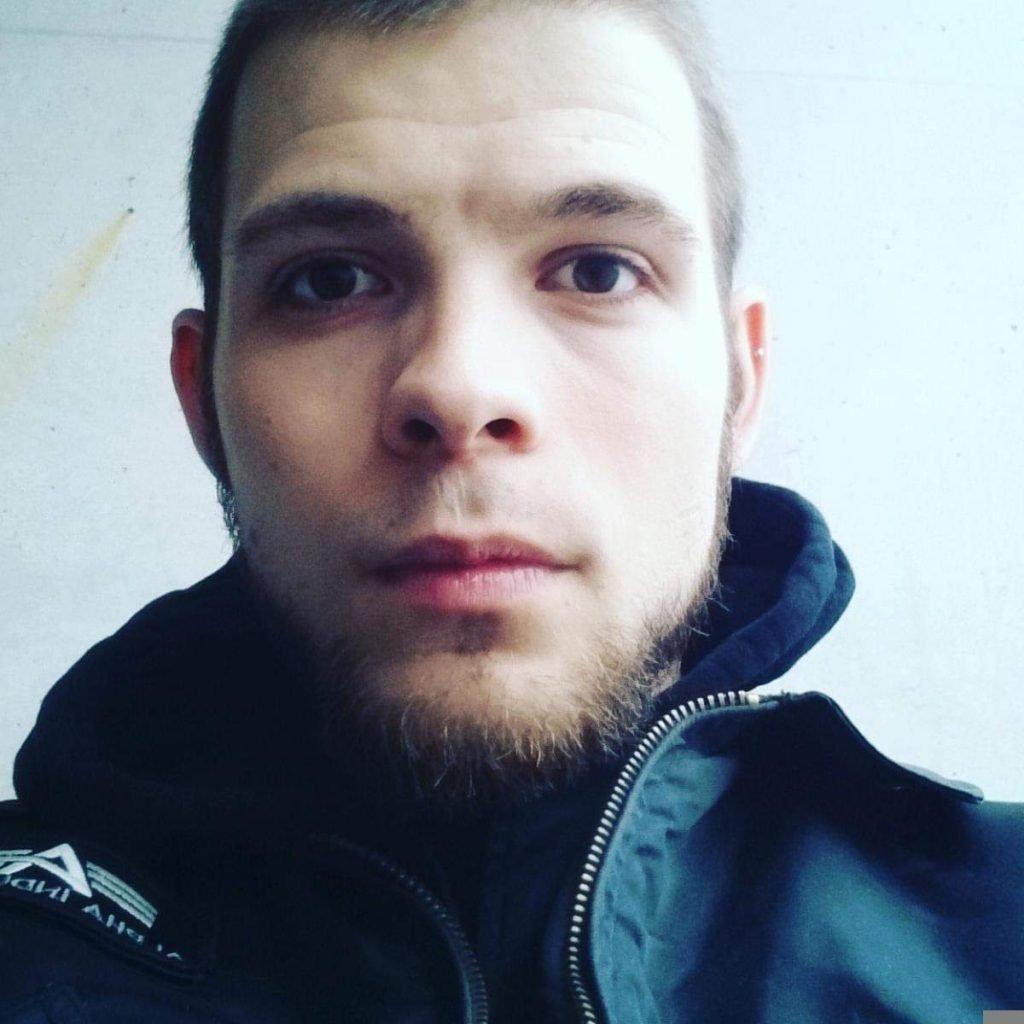 Foto vom Gesicht. Muell_Mann hat kurze mittelblonde Haare, braune Augen und einen kurzen Kinnbart. Er trägt eine blaue Jacke.