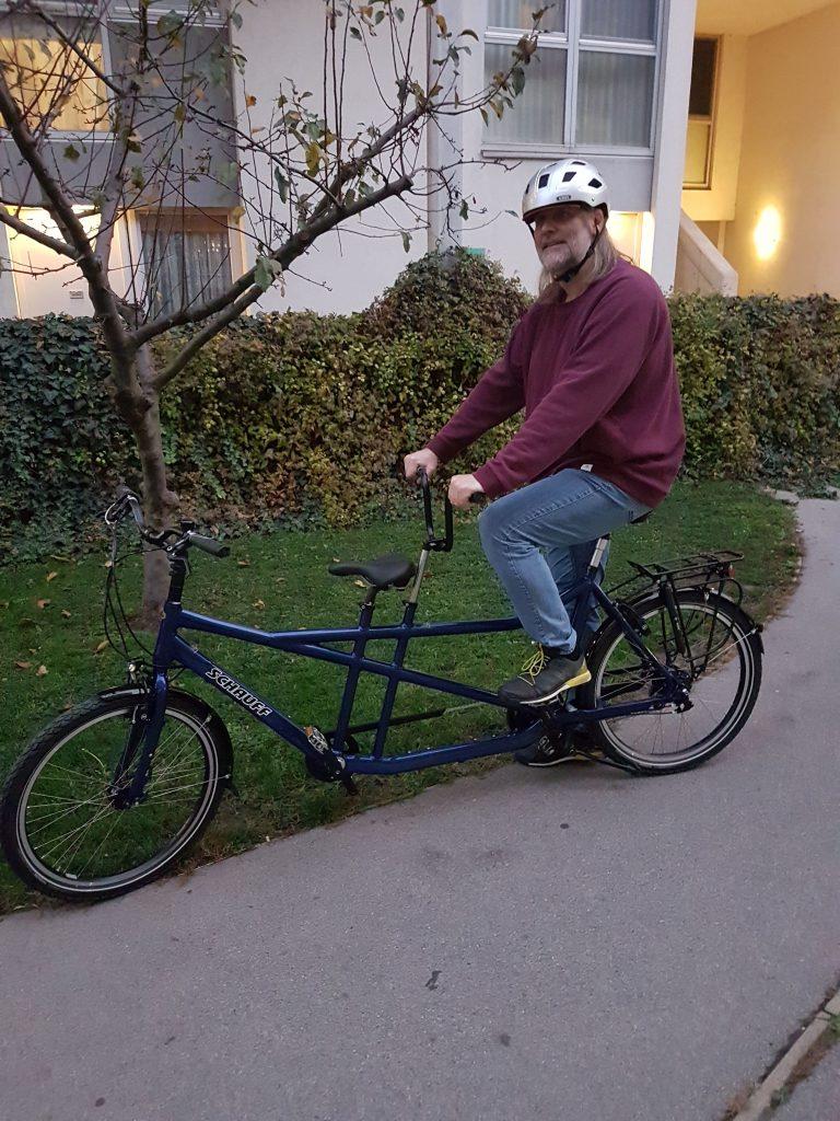 YetiFloridsdorf sitzt mit Hemd hinten auf einen Tandem-Fahrrad, das vor einem Haus steht