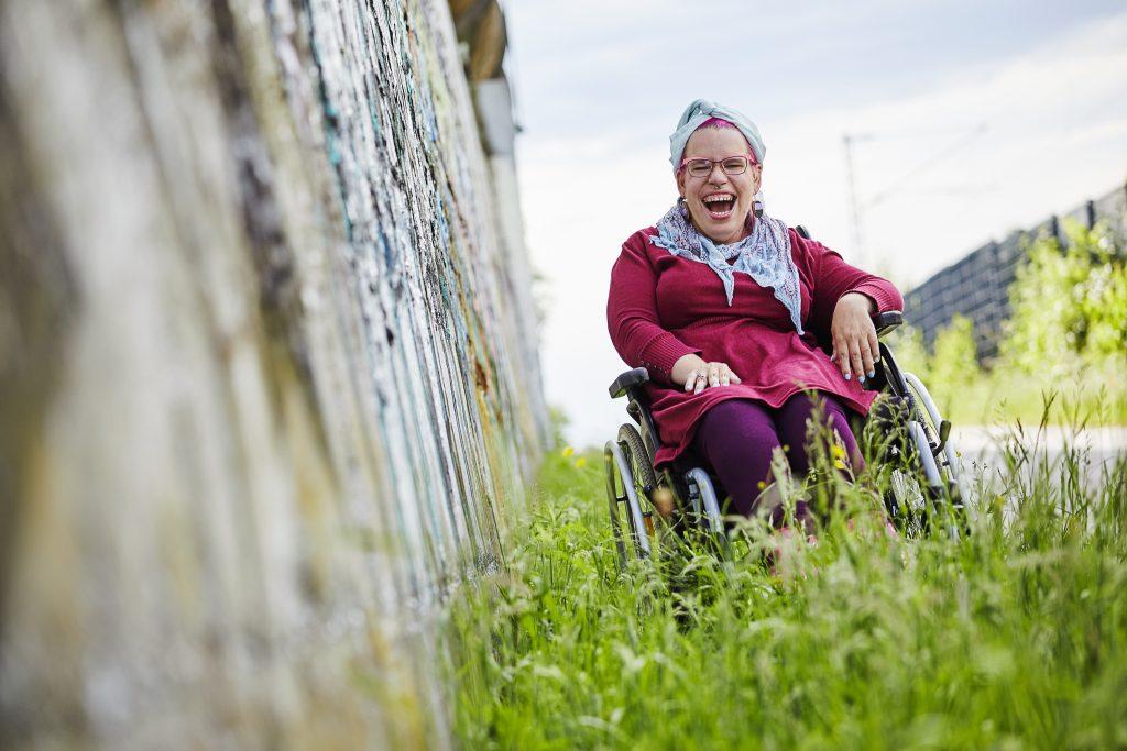 Rollifräulein steht mit dem Rollstuhl mitten im Gras. Neben ihr steht eine Mauer mit Graffiti. Sie lacht offen in die Kamera.