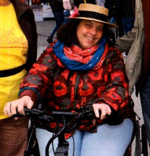 LRadern sitzt lächeln im Rollstuhl mit Zugrad. Sie trägt einen brauen Hut mit schwarzem Band, eine rot-schwarzen Jacke und einen rot-blauen Schal.