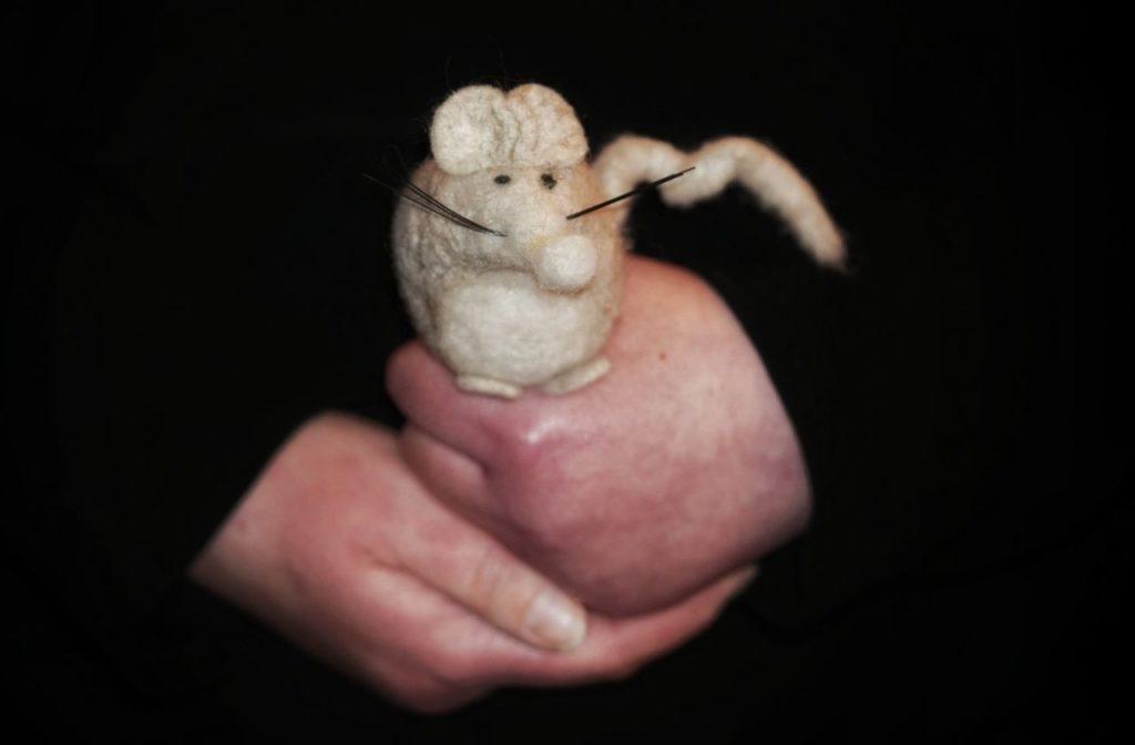 Hände, auf denen eine gehäckelte Maus steht.
