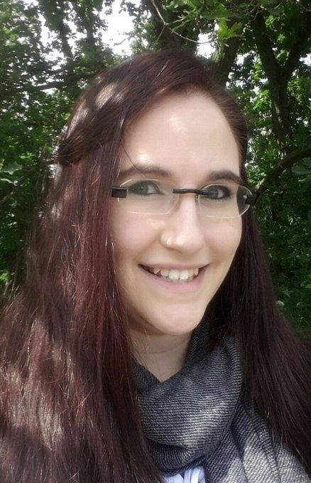 Potraitbild. Nelliehyde hat lange dunkelrote Haare. Sie lächelt und trägt eine rahmenlose Brille.