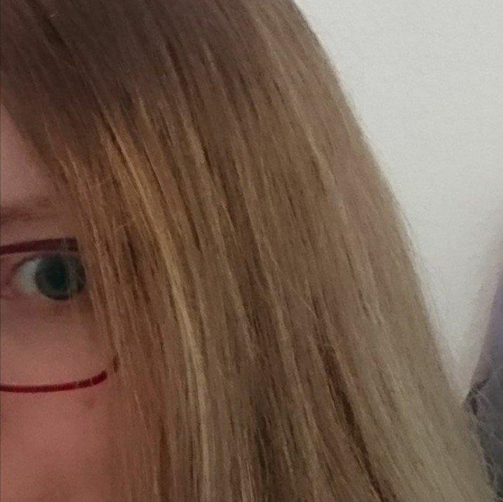 Man sieht ein Auge und ein Stück rote Brille Außerdem längere mittelblonde Haare