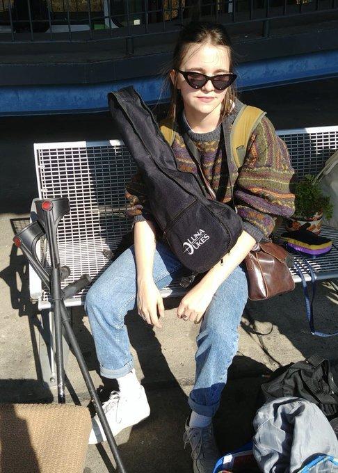 Tataeru sitzt auf einer Bank in der Sonne. Sie trägt Jeans, ein braunes Oberteil und eine Sonnenbrille.  Neben ihr stehen Gehhilfen.
